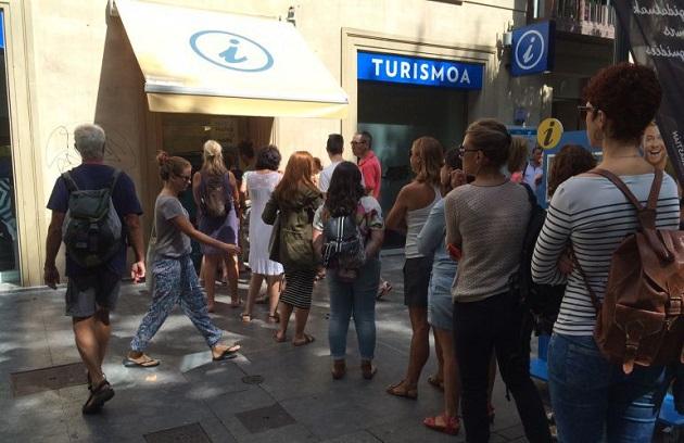 Turistas ante la oficina de Turismo
